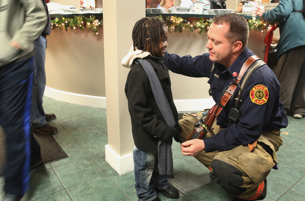 Springfield Firefighter Chad Bates talks to Jaden Peters, 3, who lives at The Stevenson Inn with his family. Bates and the crew from Station 2 supplied a holiday meal of ham and turkey meal with soup, bread and side dishes to about 50 residents of The Inn on Dec. 22, 2014. The meal was a result of a partnership between Springfield Fire Fighters Local 37, Springfield-based Midwest Medical and Bob Evans restaurant. Station 2 firefighters also purchased gifts for six children at the hotel. David Spencer/The State Journal-Register
