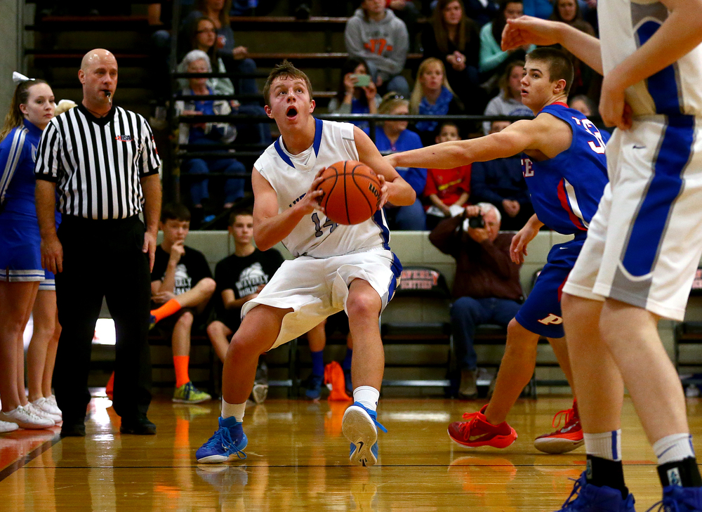 Lutheran's Josh Kirby (14) dribbles away from Pawnee's Austin Galloway (32) along the baseline as he goes for a shot in the second half during the semifinals of the 64th annual Waverly Holiday Tournament at Waverly Grade School, Monday, Dec. 29, 2014, in Waverly , Ill. Justin L. Fowler/The State Journal-Register