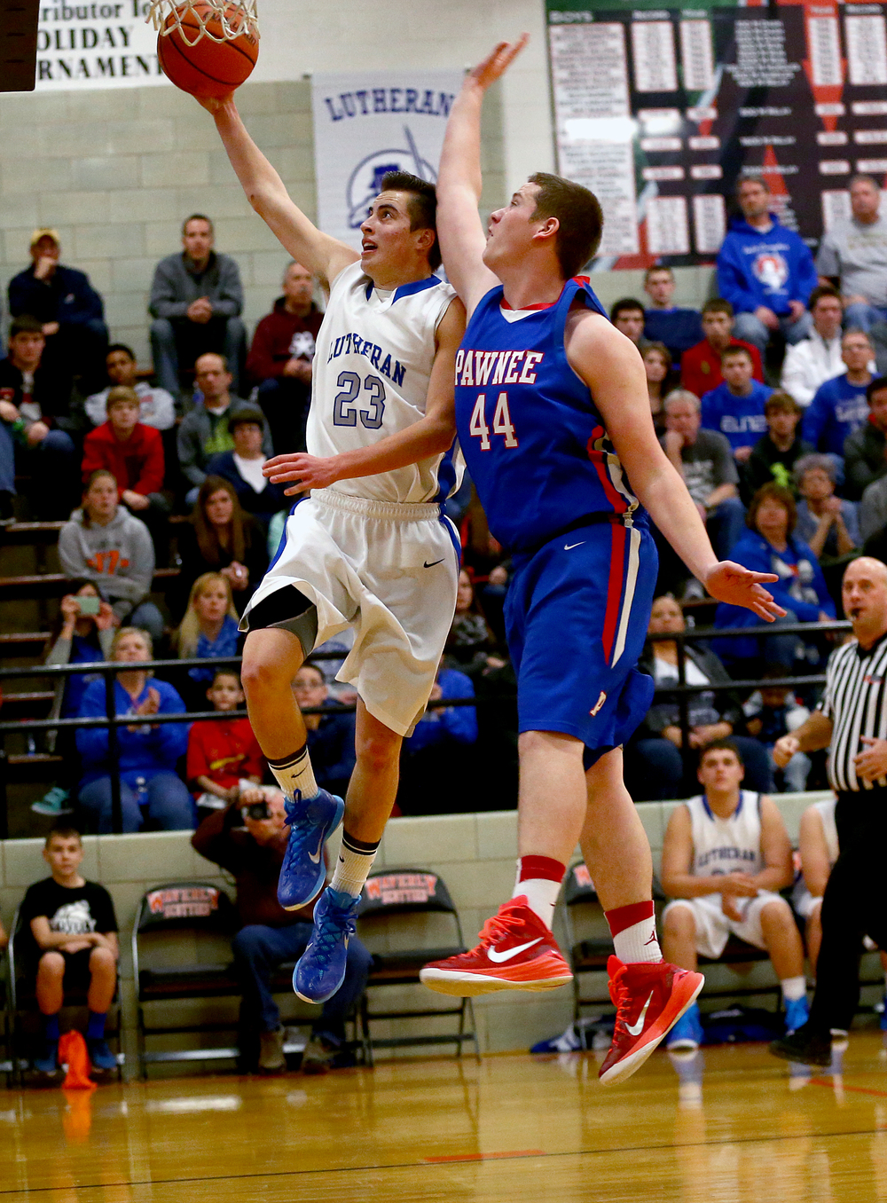 Lutheran's Steven Cowels (23) is fouled by Pawnee's Reese Bourne (44) as he goes up for a shot in the second half during the semifinals of the 64th annual Waverly Holiday Tournament at Waverly Grade School, Monday, Dec. 29, 2014, in Waverly , Ill. Justin L. Fowler/The State Journal-Register
