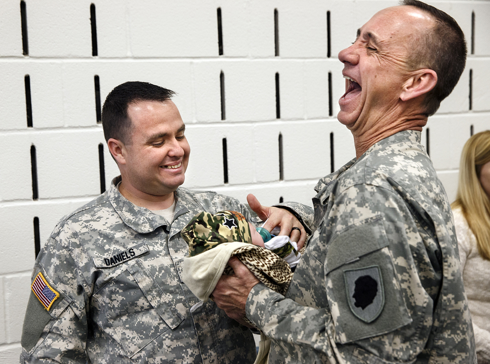 Brig. Gen. Daniel M. Krumrei, adjutant general for the Illinois National Guard, laughs as Spc. Joe Daniels of Chatham hands him his three-week old son Isaac Michael after the deployment ceremony for the Bilateral Embedded Staff Team A14 at Camp Lincoln Friday, Oct. 14, 2014. Daniels and four other soldiers will be deployed to Afghanistan through the spring of 2015. Ted Schurter/The State Journal-Register