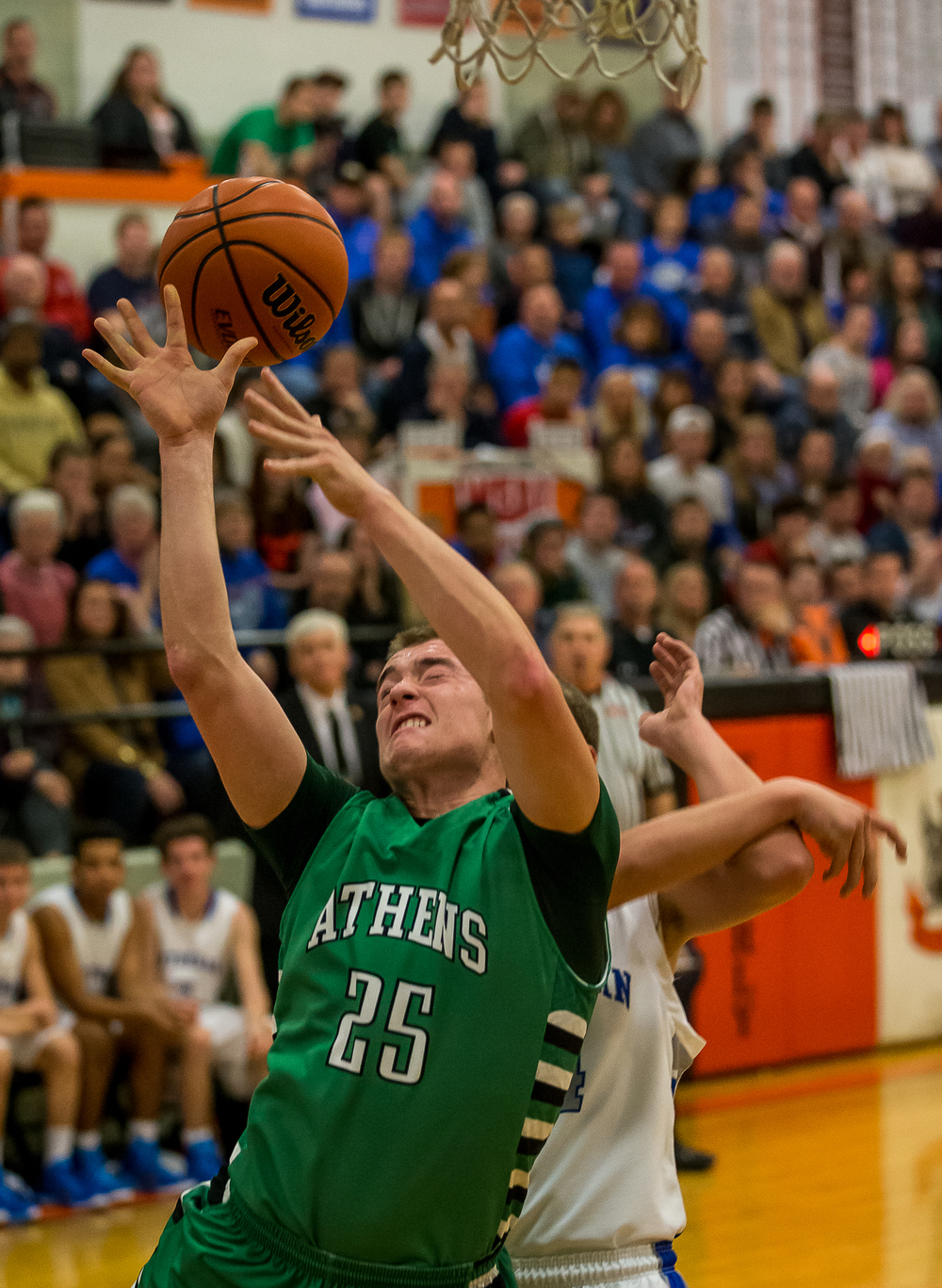 Athens' Eric Freer (25) gets fouled by Lutheran's Josh Kirby (14) going up for a shot in the first half during the championship game of the 64th annual Waverly Holiday Tournament at Waverly Grade School, Tuesday, Dec. 30, 2014, in Waverly , Ill. Justin L. Fowler/The State Journal-Register