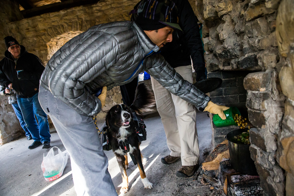 Buzz Nanavati loads a container of beans into the vegetarian pot of soup as his dog, Eddie, watches from below during the Sangamon Valley Group of the Sierra Club's Stone Soup Hike at Carpenter Park, Thursday, Jan. 1, 2015, in Springfield, Ill. Justin L. Fowler/The State Journal-Register