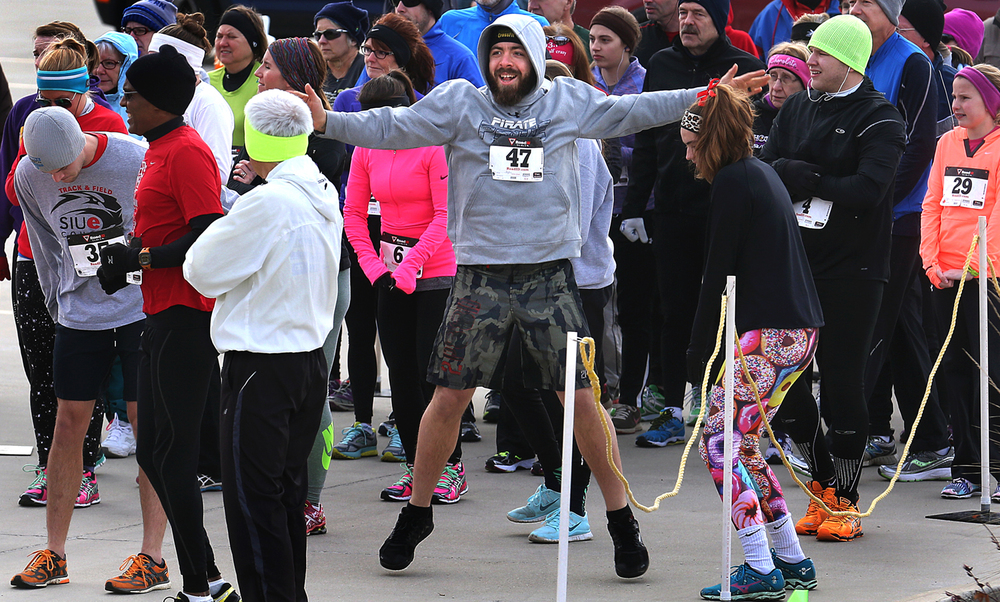 Jumping jacks seemed to be one of the preferred methods of warming up before the start of the race, including enthusiastic runner Jacob Spielbauer, center, of Green Bay, WI. Despite the freezing temperatures, 62 people signed up for the second annual Springfield Area Arts Council sponsored First Night Springfield 5K run/walk/stroll which began and ended at Scheels sporting goods on Sunday, Dec. 28, 2014. The kickoff to First Night was a partnership with the American Heart Association of Springfield. Medals, gift cards and First Night wrist bands were awarded to those finishing the 5K. David Spencer/The State Journal-