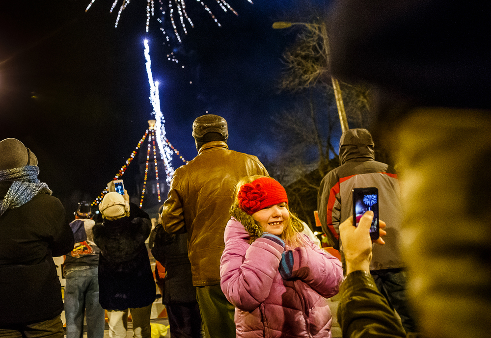 Meredith Bauer, 7, poses for her father Dylan Bauer, as he takes a picture of her and the fireworks exploding over the Illinois State Capitol during First Night Springfield at Fourth Street and Capitol Avenue, Wednesday, Dec. 31, 2014, in Springfield, Ill. Justin L. Fowler/The State Journal-Register