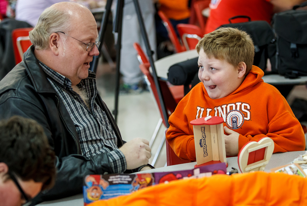 Peyton Woods, 9, gets a little help from Bill Bean, left, as he finishes off a planter that he built from a kit provided by the Lowe's Build and Grow Clinic during First Night Springfield's free children activities at Springfield High School, Wednesday, Dec. 31, 2014, in Springfield, Ill. Justin L. Fowler/The State Journal-Register