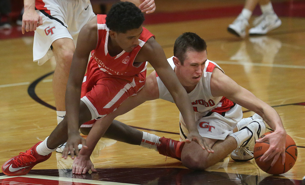 Glenwood player Sam Anderson fights for the ball on the floor with Jacksonville player James White near the end of the game. Chatham Glenwood High School defeated Jacksonville High School 36-35 in boys basketball action at Glenwood High School Tuesday evening, Jan. 6, 2015. David Spencer/The State Journal-Register