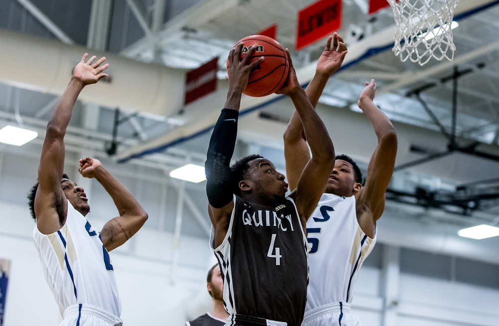 Quincy University's Thomas Jackson (4) drives up to the basket against University of Illinois Springfield's Kendall Guyton (0) and Sammie Elem (15) in the first half at the UIS Athletic & Recreation Center, Thursday, Jan. 8, 2015, in Springfield, Ill. Justin L. Fowler/The State Journal-Register