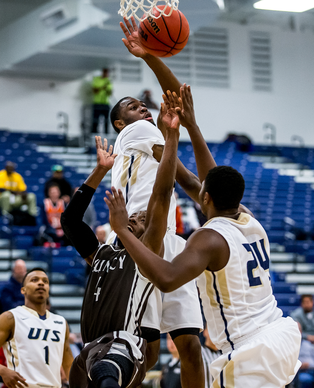 Quincy University's Thomas Jackson (4) draws the foul as he drives into the basket against University of Illinois Springfield's Colin Blaydes (30) in the second half at the UIS Athletic & Recreation Center, Thursday, Jan. 8, 2015, in Springfield, Ill. Justin L. Fowler/The State Journal-Register