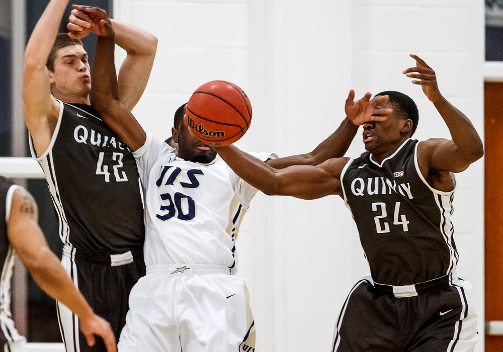 Quincy University's Godson Eneogwe (24) tries to knock the ball away from University of Illinois Springfield's Colin Blaydes (30) as he was trying to pass the ball away driving to the basket in the first half at the UIS Athletic & Recreation Center, Thursday, Jan. 8, 2015, in Springfield, Ill. Justin L. Fowler/The State Journal-Register