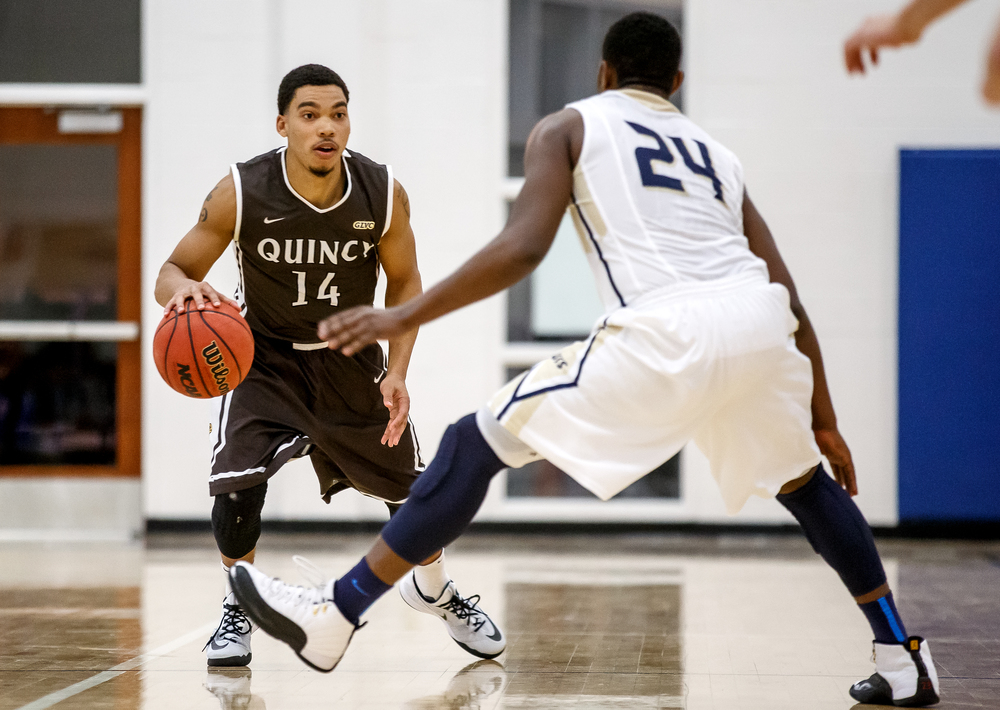 Quincy University's Herm Senor (14) moves the ball up the court against University of Illinois Springfield's Jamall Millison (24) in the first half at the UIS Athletic & Recreation Center, Thursday, Jan. 8, 2015, in Springfield, Ill. Justin L. Fowler/The State Journal-Register