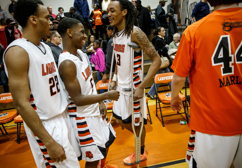 Lanphier's Aarin Thames (3) celebrates with Xavier Bishop (5) while on crunches after the Lions defeated Lincoln 40-35 in the second half at Lober-Nika Gymnasium, Friday, Jan. 9, 2015, in Springfield, Ill. Thames left the game after being injured in the first half. Justin L. Fowler/The State Journal-Register