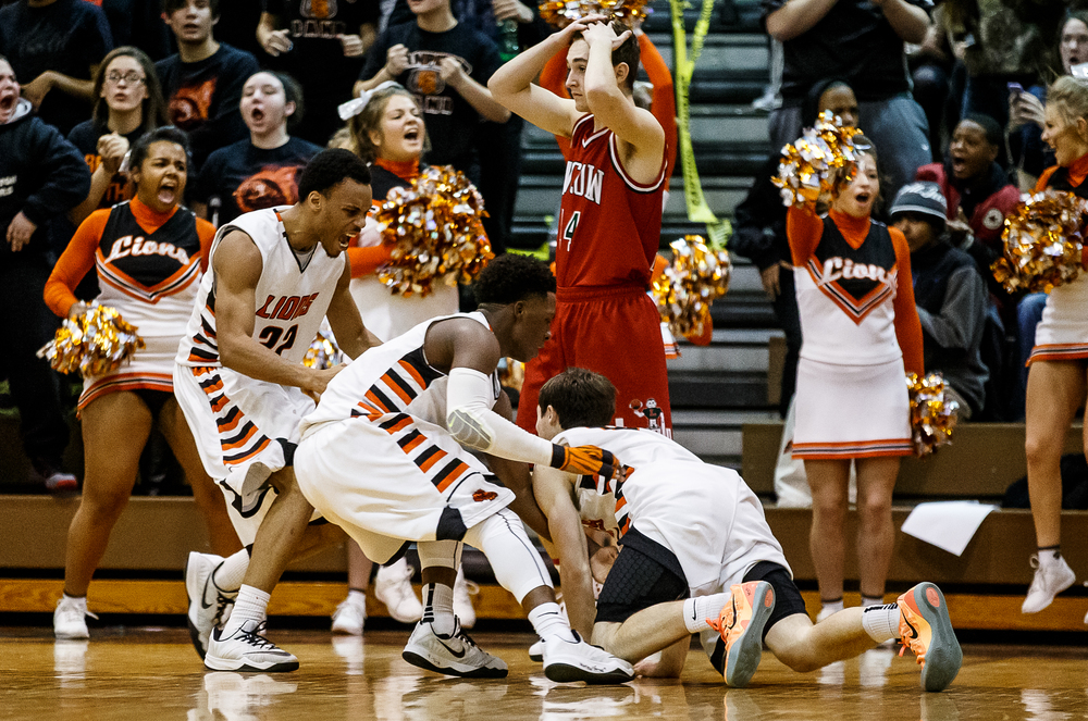 Lanphier's Nick Patton (15) is mobbed by his teammates Daryl Jackson (22) and Yaakema Rose (1) after drawing the foul on Lincoln while shooting a three with 1.9 second left in the second half at Lober-Nika Gymnasium, Friday, Jan. 9, 2015, in Springfield, Ill. Justin L. Fowler/The State Journal-Register