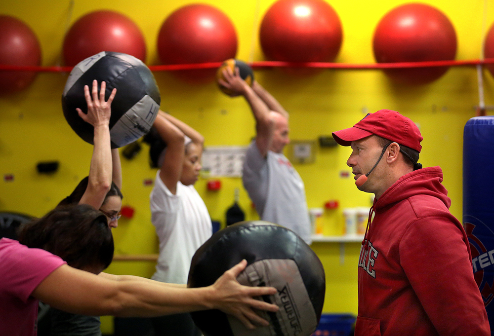 At HIPE, a gym on Springfield's westside standing for High Intensity Practical Exercises, owner Wayne Carrels, right, continually offers encouragement while walking among those working out using medicine balls during a class on Saturday, Jan. 3, 2015. David Spencer/The State Journal-Register