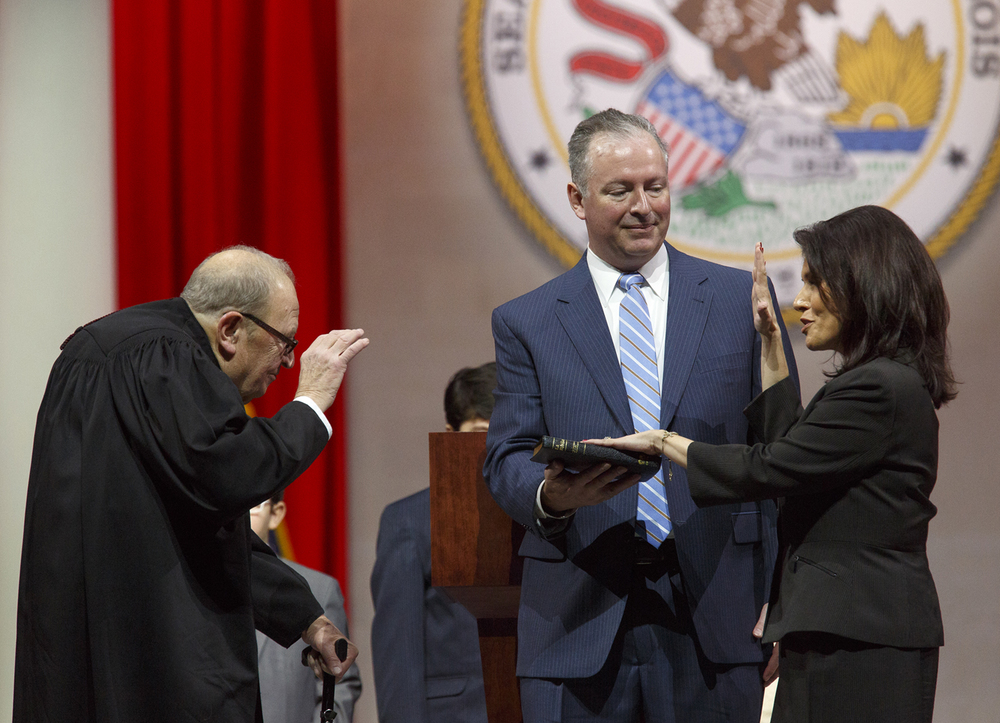 Dupage County Judge Lewis Morgan administers the oath of office to Lt. Gov. Evelyn Sanguinetti Monday, Jan. 12, 2015 at the Prairie Capital Convention Center in Springfield, Ill. Sanguinetti's husband, Raymond, holds the Bible. Rich Saal/The State Journal-Register