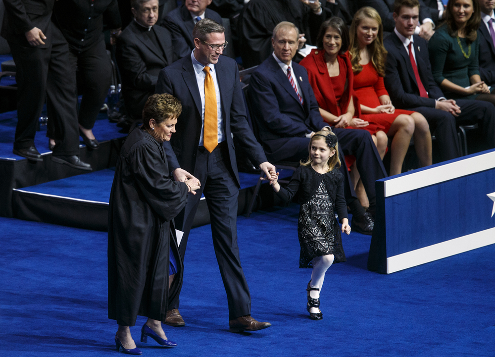 Mike Frerichs is flanked by  Illinois Supreme Court Chief Justice Rita Garman, left, and his daughter Ella as he approaches the podium to take the oath of office as treasurer Monday, Jan. 12, 2015.  Ted Schurter/The State Journal-Register