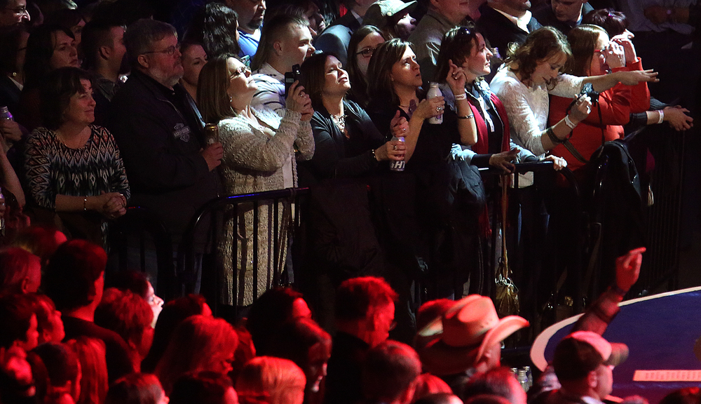 Inauguration concert patrons near the front of the stage are bathed in light while listening to Toby Keith perform.  Replacing the traditional inaugural ball, a concert with country singer Toby Keith as headliner took place at the Prairie Capital Convention Center in Springfield marking Bruce Rauner becoming the 42nd governor of Illinois Monday evening, Jan. 12, 2015. David Spencer/The State Journal-Register