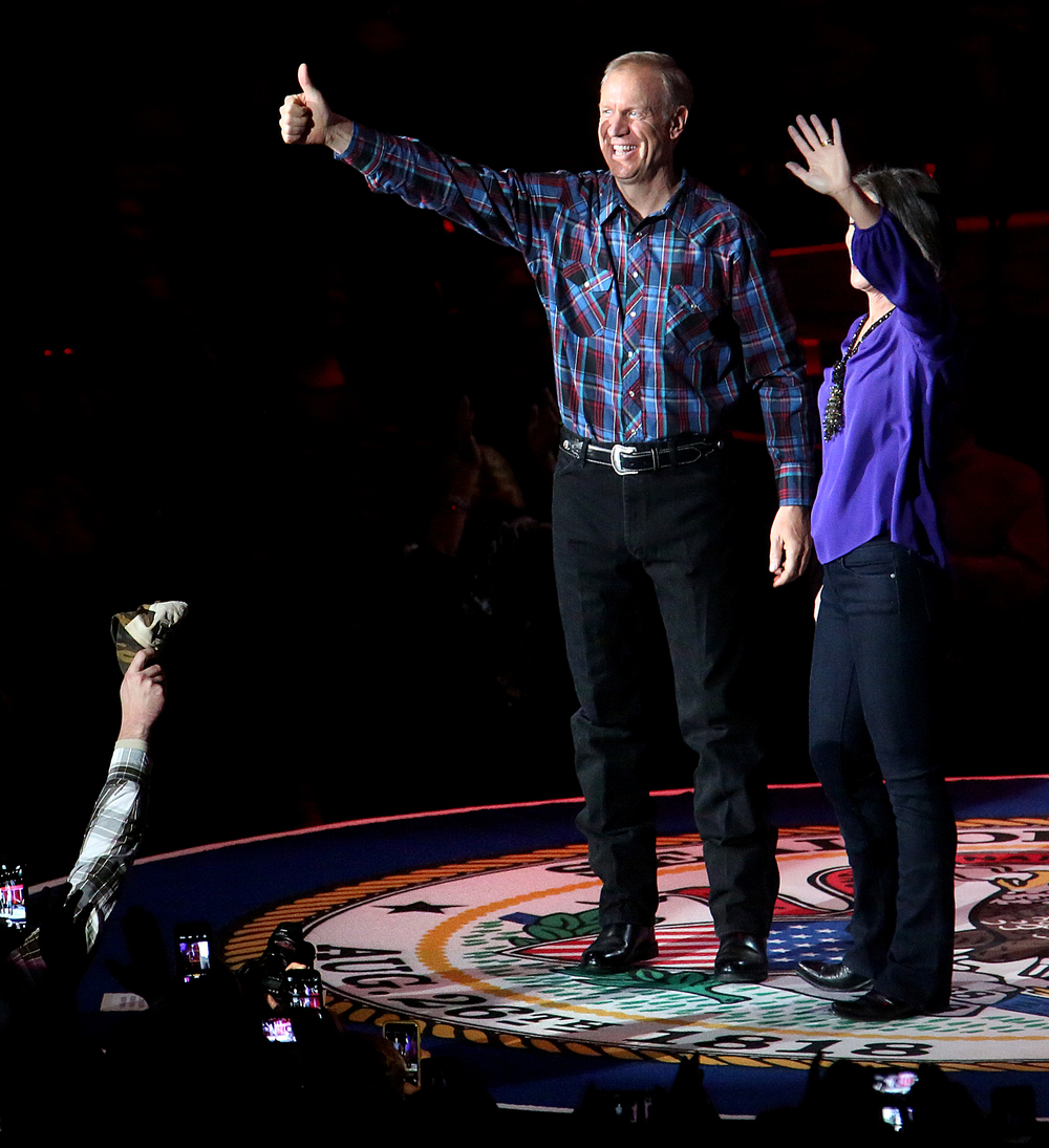 Illinois governor Bruce Rauner gives the thumbs up and wife Diana Rauner waves after they are introduced onstage by Toby Keith Monday night. Replacing the traditional inaugural ball, a concert with country singer Toby Keith as headliner took place at the Prairie Capital Convention Center in Springfield marking Bruce Rauner becoming the 42nd governor of Illinois Monday evening, Jan. 12, 2015. David Spencer/The State Journal-Register