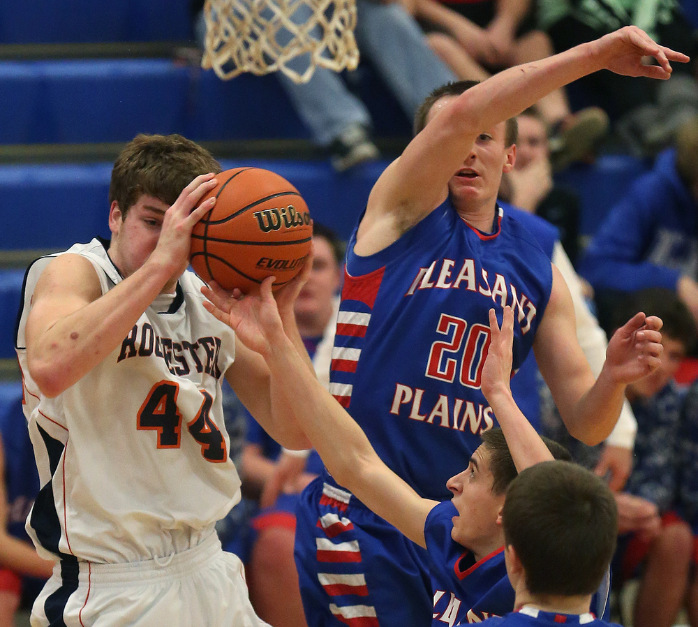 Pleasant Plains player Isaac Collins at center tries to disrupt a rebound snagged by Rochester player Adam Conrady. Rochester defeated Pleasant Plains 61-37 in a semifinal game at the Sangamon County Basketball Tournament at Cass gymnasium at Lincoln Land Community College in Springfield on Wednesday evening, Jan. 14, 2015. David Spencer/The State Journal-Register