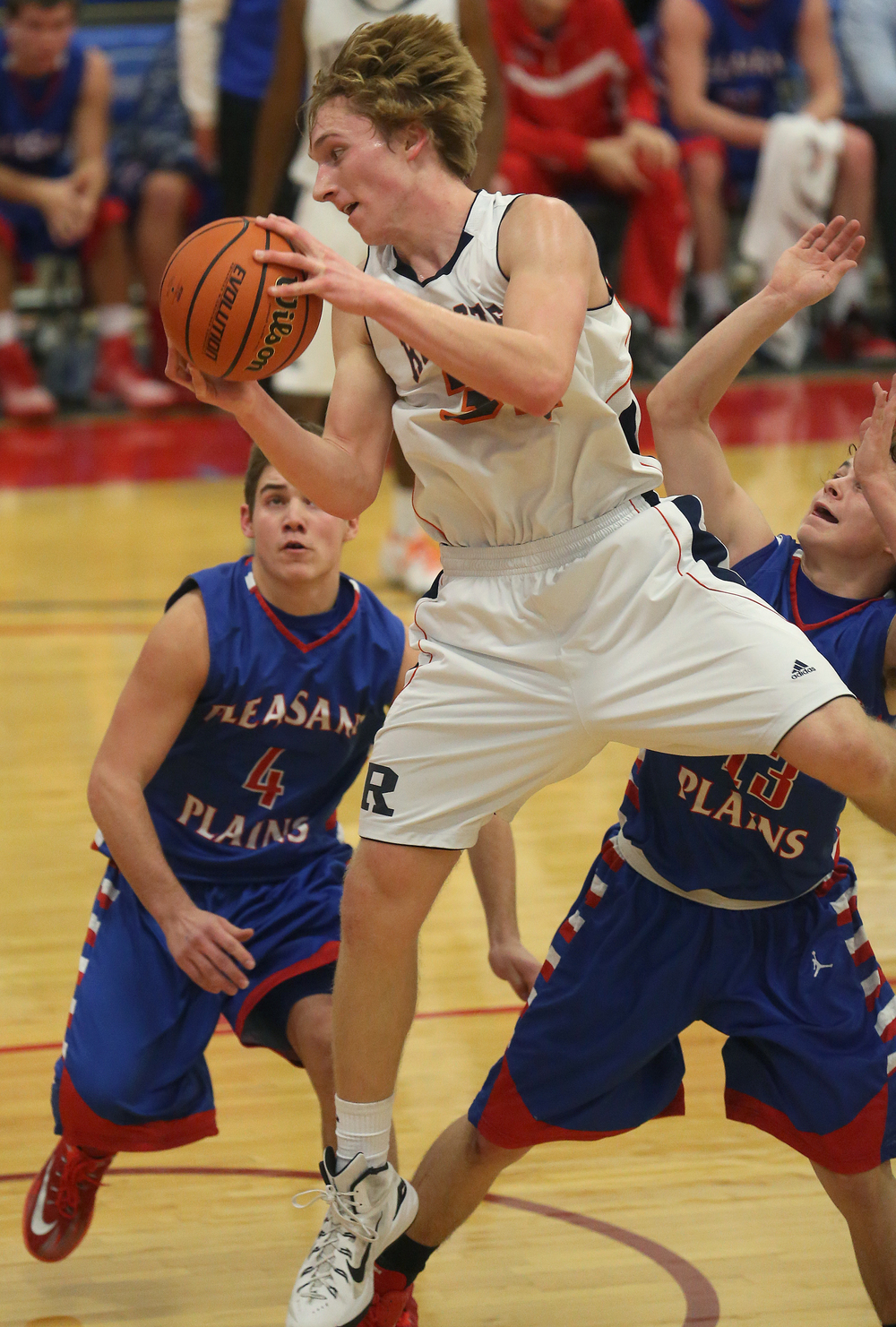 Rochester's Matt McClintock sails past Plains defenders Aden Sachs at left and Cole Greer in route to putting two points during late first half action Thursday night. Rochester defeated Pleasant Plains 61-37 in a semifinal game at the Sangamon County Basketball Tournament at Cass gymnasium at Lincoln Land Community College in Springfield on Wednesday evening, Jan. 14, 2015. David Spencer/The State Journal-Register
