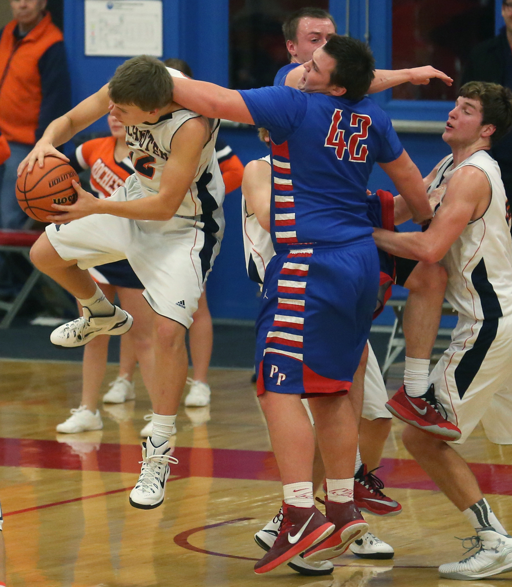 Rochester player Dan Zeigler grabs a rebound while being strong armed by Plains defender Nik Clemens. Rochester defeated Pleasant Plains 61-37 in a semifinal game at the Sangamon County Basketball Tournament at Cass gymnasium at Lincoln Land Community College in Springfield on Wednesday evening, Jan. 14, 2015. David Spencer/The State Journal-Register