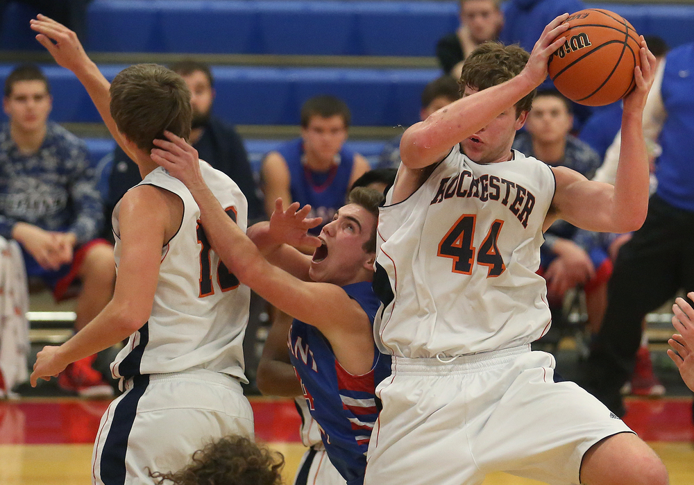 Rochester player Adam Conrady grabs a rebound while sandwiching Plains player Isaac Collins between teammate Dan Zeigler.  Rochester defeated Pleasant Plains 61-37 in a semifinal game at the Sangamon County Basketball Tournament at Cass gymnasium at Lincoln Land Community College in Springfield on Wednesday evening, Jan. 14, 2015. David Spencer/The State Journal-Register