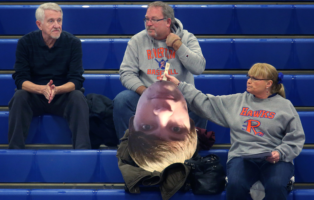 "Sean Nation, who plays on the Riverton Hawks basketball team, is sometimes in two places at once-occasionally present in the stands in the form of a large photographic cut-out of his head made into a hand sign as well as on the court, thanks to mom Wendy Nation. Wendy Nation, right, arrived early to the quarterfinal game at the Sangamon County Basketball Tournament at Cass gymnasium at Lincoln Land Community College in Springfield on Tuesday evening, Jan. 13, 2015. Camped out ""on the 50 yard line"", Nation's team unfortunately came up a bit short against the Auburn High School Trojans.  David Spencer/The State Journal-Register"