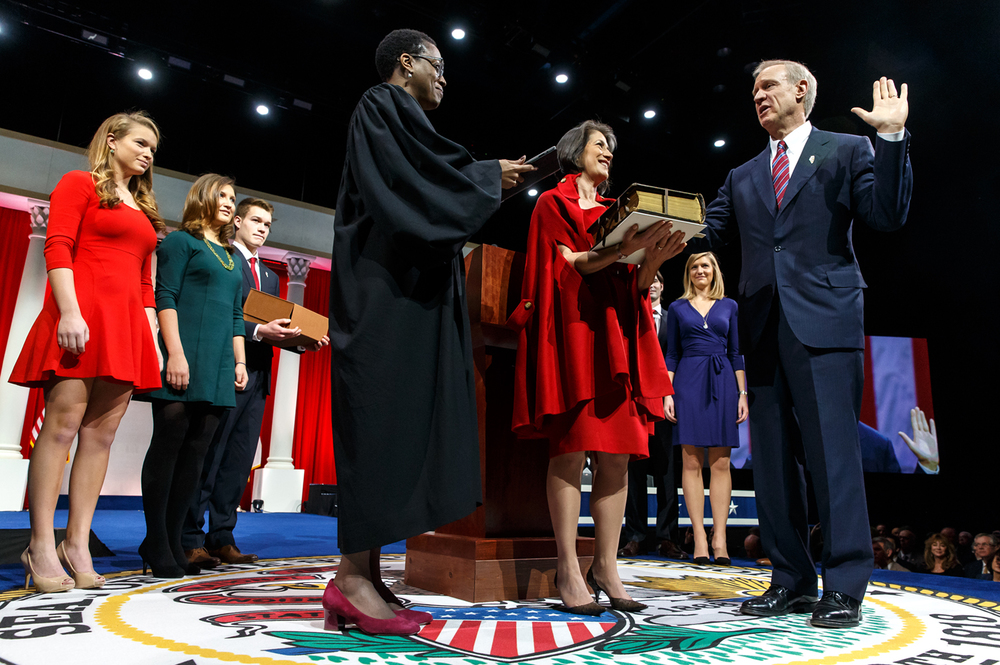 Illinois Gov.-elect Bruce Rauner takes the Oath of Office from the Honorable Sharon Johnson Coleman with his wife, Diana, holding the Bible and surrounded by his children during the Illinois Inaugural Ceremony at the Prairie Capital Convention Center, Monday, Jan. 12, 2015, in Springfield, Ill. Justin L. Fowler/The State Journal-Register