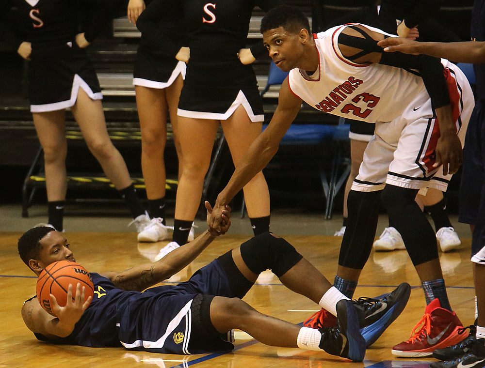 Springfield player Obediah Church helps up fallen Southeast player Sabree Bakari late in the game. Springfield High School defeated Southeast 66-55 during first night action at the Boys City Basketball Tournament at the Prairie Capital Convention Center in Springfield on Thursday, Jan. 22, 2015. David Spencer/The State Journal-Register