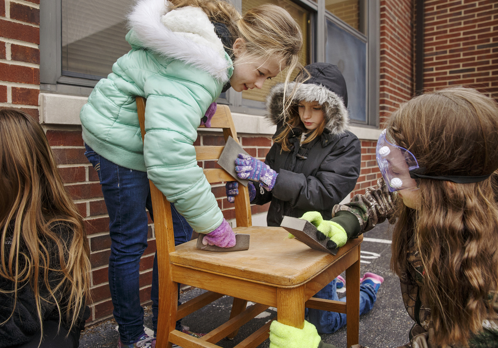 Molly Green, left, Jillian Carter and Amya Filbrun work together to sand an old wooden school chair at Chatham Ball Elementary Friday, Jan. 23, 2015. The chairs will be decorated by students and then sold as a fundraiser to benefit the school district. Ted Schurter/The State Journal-Register