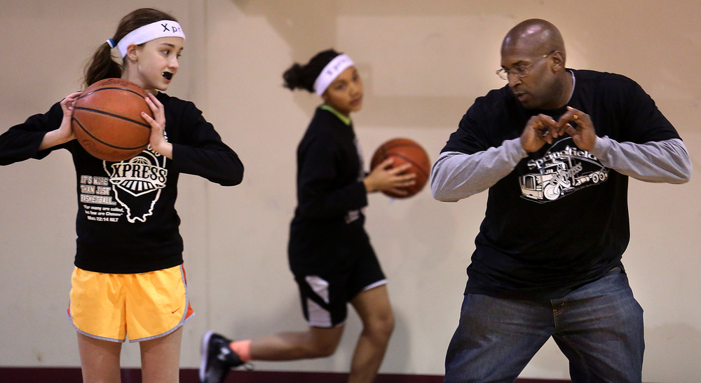 Coach Tariq Toran gives some advice on ball handling to team member Laura Kaiser, 10. The Central Illinois Xpress girls basketball team, made up of local fifth grade students, has consistently been beating boys teams from the Midwest. They practice here at Abundant Faith Christian Center gymnasium in Springfield on Friday, Jan. 24, 2015.  David Spencer/The State Journal-Register