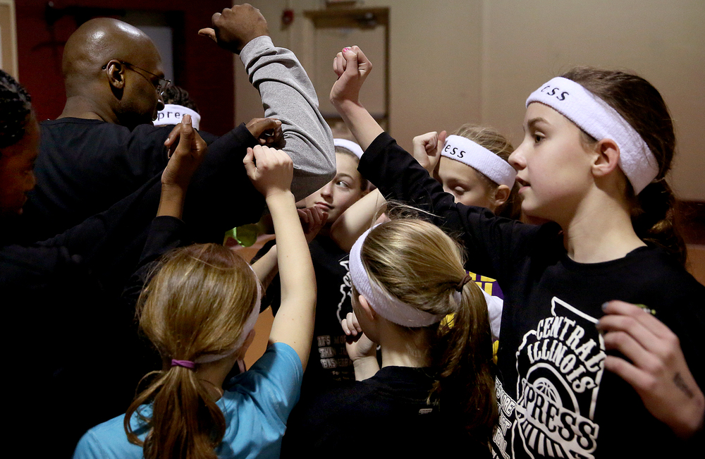 At the conclusion of the practice Friday evening, Coach Tariq Toran, left, gathers his players together with all hands in and says words of encouragment along with a short prayer. The Central Illinois Xpress girls basketball team, made up of local fifth grade students, has consistently been beating boys teams from the Midwest. They practice here at Abundant Faith Christian Center gymnasium in Springfield on Friday, Jan. 24, 2015.  David Spencer/The State Journal-Register
