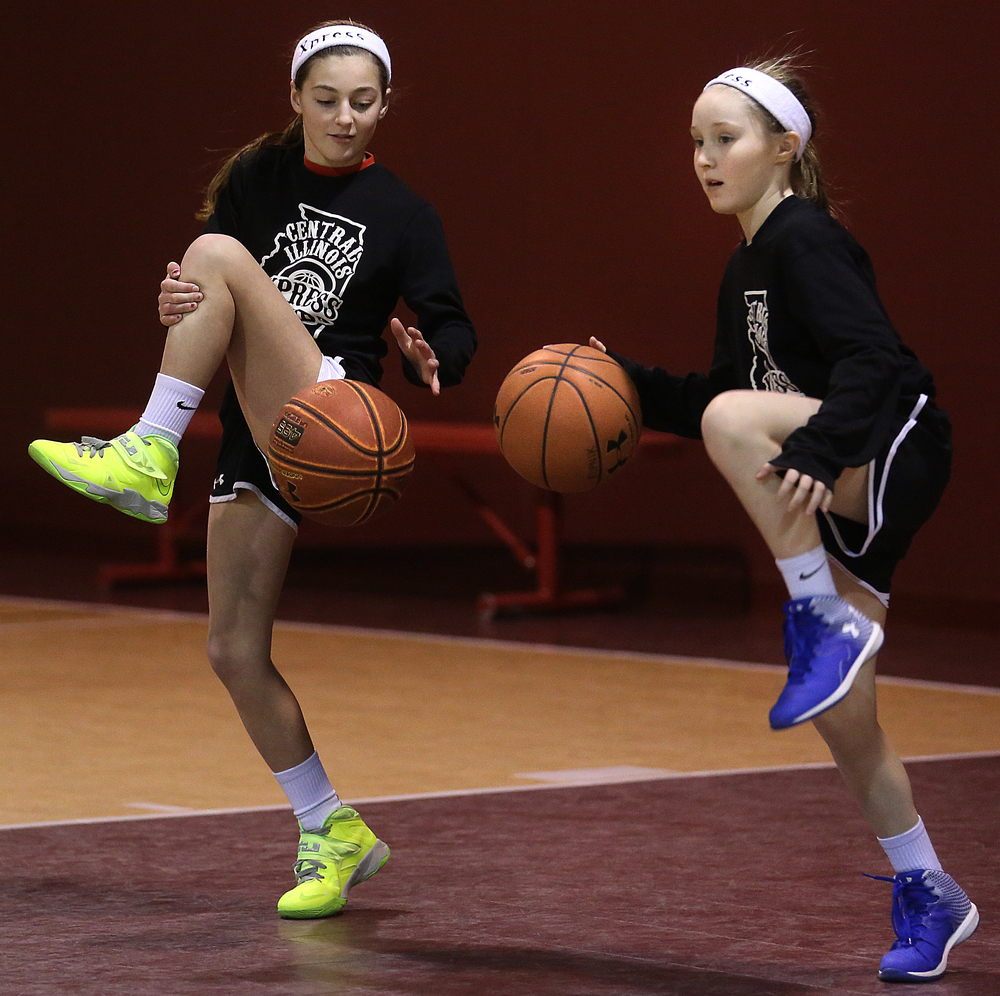 A one-legged dribbling drill has Lauren Schrage, left, and Anne Rupnik doing their best. The Central Illinois Xpress girls basketball team, made up of local fifth grade students, has consistently been beating boys teams from the Midwest. They practice here at Abundant Faith Christian Center gymnasium in Springfield on Friday, Jan. 24, 2015.  David Spencer/The State Journal-Register