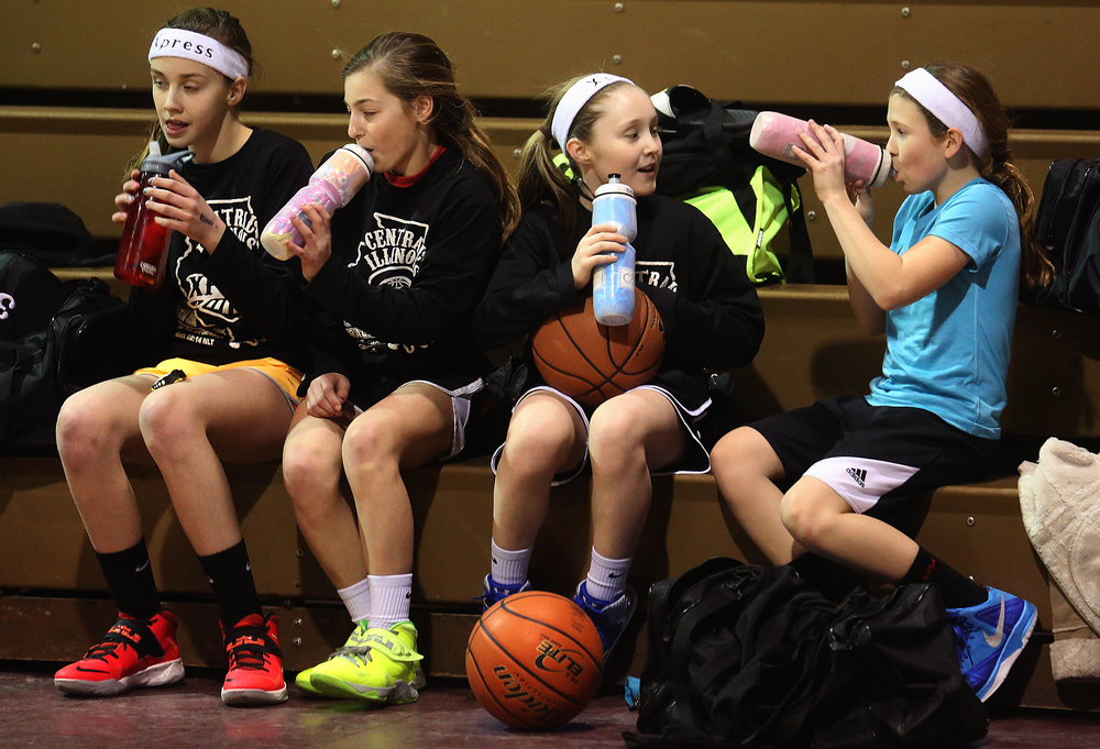 Members of the team take a water break. From left to right: Laura Kaiser, Lauren Schrage, Anne Rupnik, Anna Chambers. The Central Illinois Xpress girls basketball team, made up of local fifth grade students, has consistently been beating boys teams from the Midwest. They practice here at Abundant Faith Christian Center gymnasium in Springfield on Friday, Jan. 24, 2015.  David Spencer/The State Journal-Register