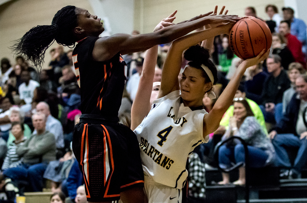 Southeast's Alexis Henry (4) services the pressure form Lanphier's Jeniya Griffin (5) as she kicks the ball out to a teammate in the second half during the 2015 Girls City Tournament at Jim Belz Gymnasium, Thursday, Jan. 29, 2015, in Springfield, Ill. Justin L. Fowler/The State Journal-Register