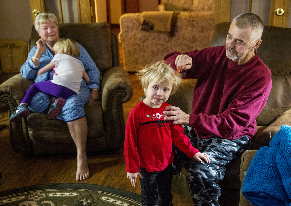 Joseph Smith combs his daughter Abigail Montgomery's hair as his wife Linda gets a hug from her sister Carly Friday, Jan. 30, 2015. Smith, the first person in central Illinois to receive a surgical treatment that rinsed his abdominal cavity with heated chemotherapy to treat Stage 4 cancer, and his wife Linda care for the girls and their other two sisters who lost their mother to cancer. Ted Schurter/The State Journal-Register