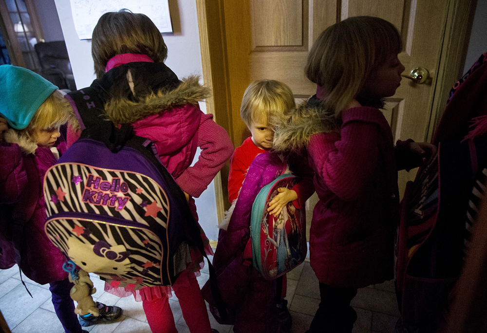 Carly, Elizabeth, Abigail and Isabella Montogmery get their coats and backpacks ready Friday, Jan. 30, 2015. The girls, who lost their mother to cancer, were adopted by Joseph and Linda Smith. Joseph is the first person central Illinois to receive a surgical treatment that rinsed his abdominal cavity with heated chemotherapy to treat his Stage 4 cancer. Ted Schurter/The State Journal-Register