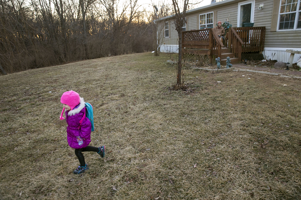 Carly Montogmery makes her way to the bus stop to wait with her three sisters as her dad Jim watches from the porch Friday, Jan. 30, 2015. The girls, who lost their mother to cancer, were adopted by Joseph and Linda Smith. Joseph is the first person central Illinois to receive a surgical treatment that rinsed his abdominal cavity with heated chemotherapy to treat his Stage 4 cancer. Ted Schurter/The State Journal-Register