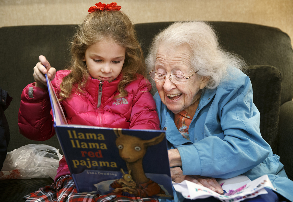 "Natalie Zak reads the book ""Llama Llama Red Pajama"" to Cillia Helfand at the Hickory Glen apartments Monday, Jan. 26, 2015. More than two dozen first grade St. Agnes Catholic School students brought books to read to residents as part of the kickoff to National Catholic Schools Week. Ted Schurter/The State Journal-Register"