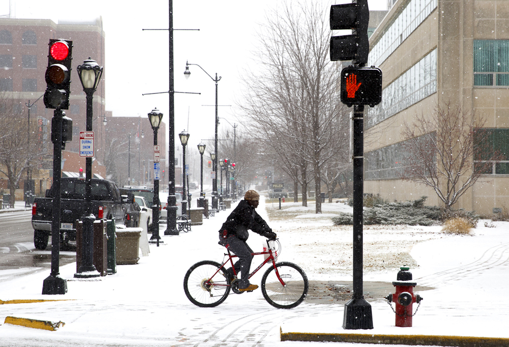 A bicyclist rides on the sidewalk along Seventh Street during a light snow Monday, Jan. 26, 2015. Rich Saal/The State Journal-Register