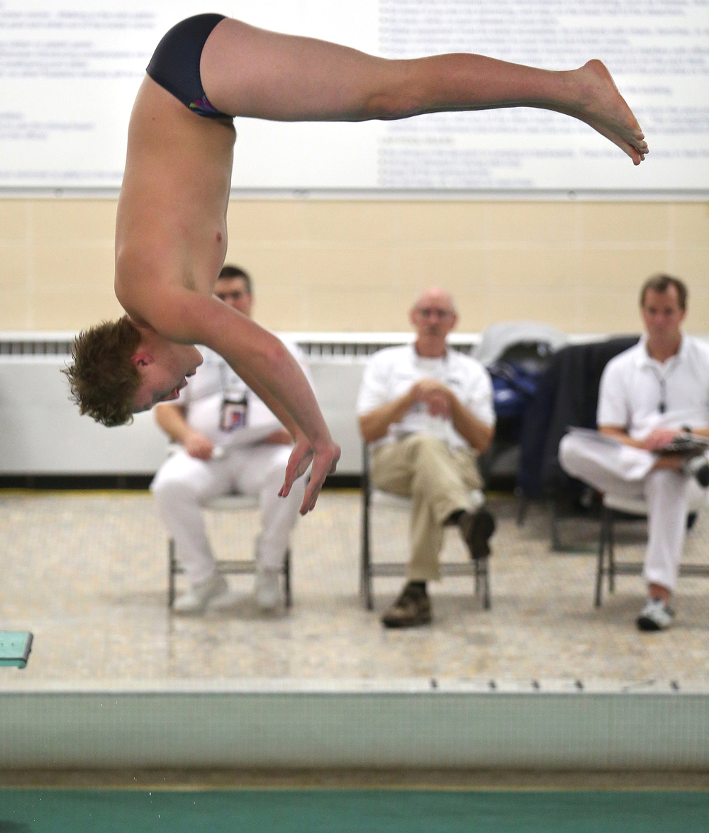 Springfield High School junior Atticus Teichman performs a dive for the judges Tuesday night. Teichman won the overall event with a score of 255.25 points. The Boys City Swim Meet was held at Eisenhower Pool in Springfield on Tuesday evening, Jan. 27, 2015. David Spencer/The State Journal-Register