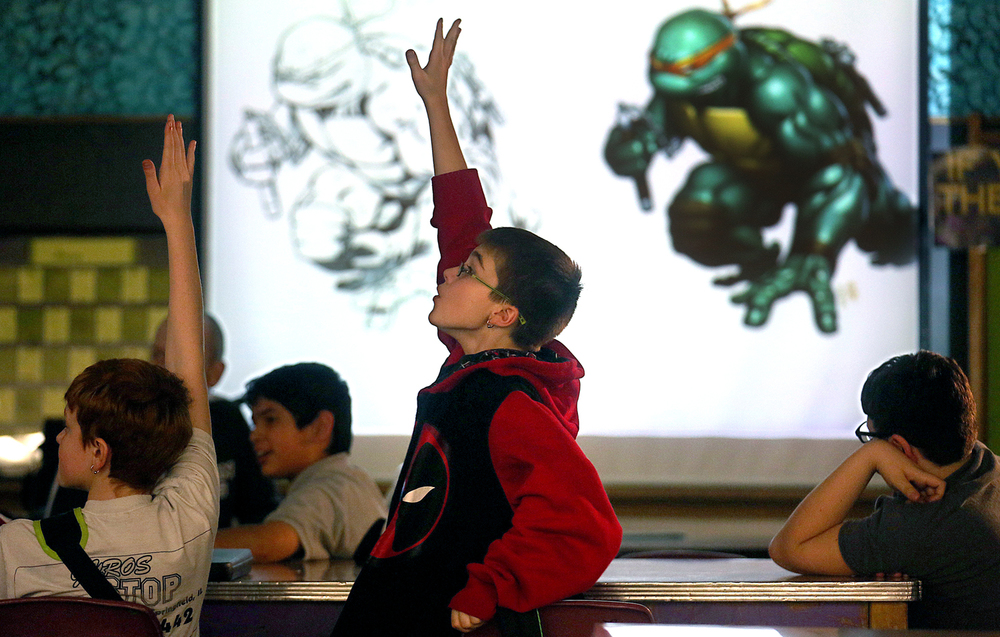 During a slide presentation on comics given by Atkins Thursday, sixth grade student Anakin Horner at center made sure he let Atkins know he knew who the Teenage Mutant Ninja Turtles were as a slide of the action heroes appeared on screen. Springfield resident Robert Atkins, a comic artist and illustrator who has done work for Marvel Comics, including on the Amazing Spider-Man, Venom and She-Hulk as well as G.I. Joe and Snake Eyes for toymaker Hasbro, gave a presentation to art club members and other students at Grant Middle School in Springfield on Thursday, Jan. 29, 2015. Atkins received degrees from Illinois State University and the Savannah College of Art and Design. David Spencer/The State Journal-Register