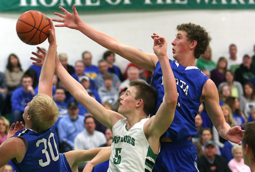 Athens player Matt Wendling is sandwiched during a rebound opportunity by PORTA players Max Muller at right and Michael McCurdy. Petersburg PORTA defeated Athens 64-32 in boys basketball action at Athen's gym in Athens on Tuesday evening, Feb. 3, 2015. David Spencer/The State Journal-Register