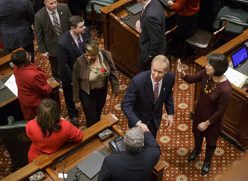 Illinois Gov. Bruce Rauner and First Lady Diana Rauner greet legislators as they exit the Illinois House of Representatives after the State of the State speech Wednesday, Feb. 4, 2015. Ted Schurter/The State Journal-Register