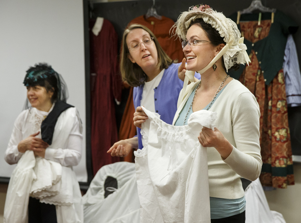 University of Illinois Springfield adjunct faculty member Sarah Eccles laughs as visiting instructor Helena Hall discusses the social significance of how Civil War era women fastened their bonnets as she ties one to her head during a history presentation to Intensive English Program students Friday, Feb. 6, 2015. Ted Schurter/The State Journal-Register
