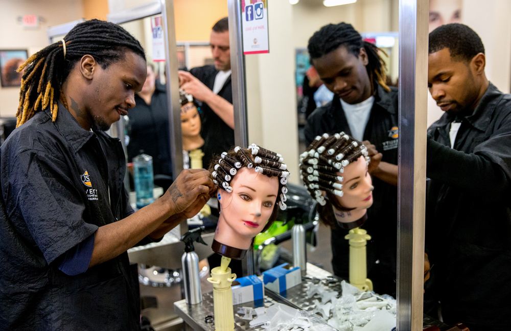 """Don Criss Jr., left, and James Green, right, practice giving mannequins a perm while studying the barbering program at the University of Spa & Cosmetology Arts, Thursday, Feb. 5, 2015, in Springfield , Ill. Though perms are not a common practice by barbers the students still learn the techniques involved. """"I'm tired of working 9-5 jobs. I wanted to start a career,"""" Criss said of his reasons for joining the program. His long term goal to open up his own barber shop in Springfield. Justin L. Fowler/The State Journal-Register"""