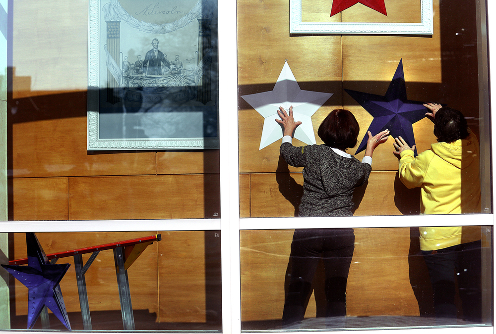 Volunteers Naydene Moss, left, and Carol Sobeck position stars on Tuesay afternoon. Decorating in preparation for Abraham Lincoln's birthday on February 12 began several months ago for areas in and around the Abraham Lincoln Presidential Museum and Library and Union Station. On Tuesday, Feb. 3, 2015, volunteers were busy at work arranging the eventual placement of oversized stars in patriotic colors in the large windows of the museum near the entrance along E. Jefferson St. in Springfield. Patriotic bunting has been hung inside the museum; large cut-out tophats will be placed in the exterior windows of the library and patriotic streamers will be hung from light poles around the three sites. David Spencer/The State Journal-Register