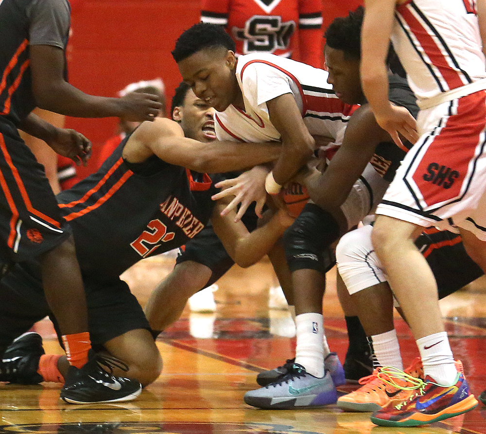 Springfield player Javoun Watters at center tries to hold onto the ball while Lanphier player Daryl Jackson at left has another idea. Lanphier defeated Springfield High School 64-54 in boys basketball action at Springfield's Willard Duey Gym on Tuesday evening, Feb. 10, 2015. David Spencer/The State Journal-Register