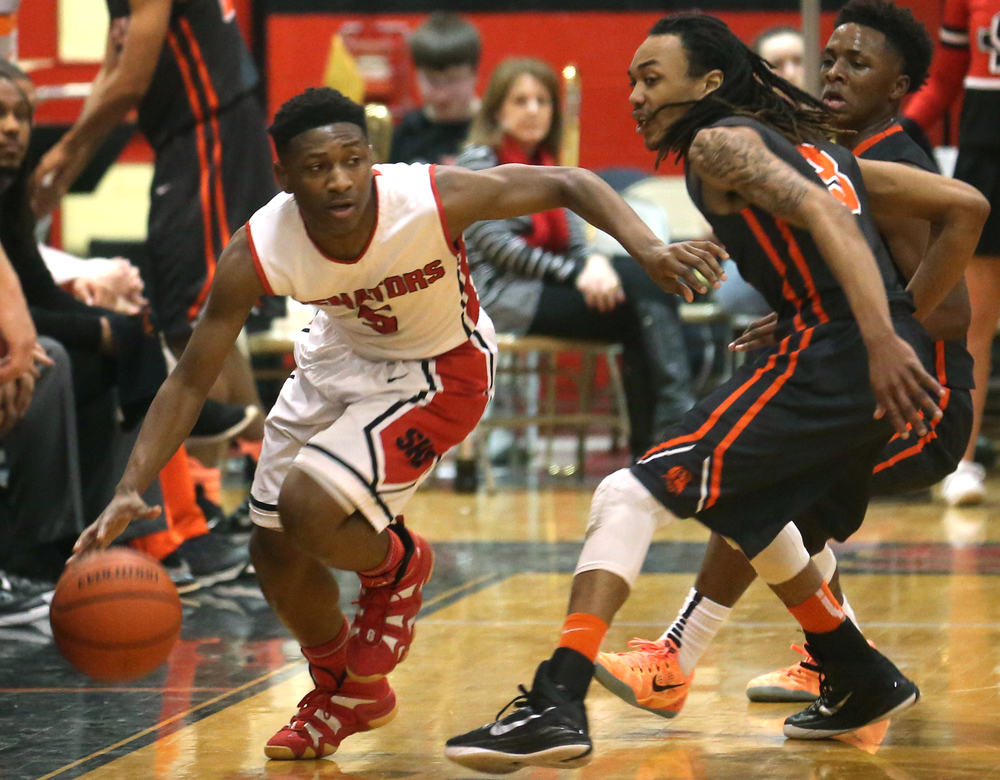 Springfield player Isaac Nelson drives around Lanphier defender Aarin Thames. Lanphier defeated Springfield High School 64-54 in boys basketball action at Springfield's Willard Duey Gym on Tuesday evening, Feb. 10, 2015. David Spencer/The State Journal-Register