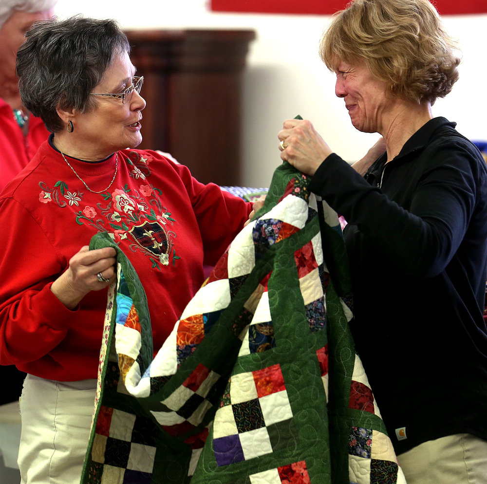 "A tearful Tina Kern at right is presented with a special ""Rosalie's Legacy"" quilt in memory of her mother Rosalie Conklin made by members of the Sangamon County Association of Home and Community Education by Linda Sichlan  at the nursing home on Wednesday. David Spencer/The State Journal-Register"