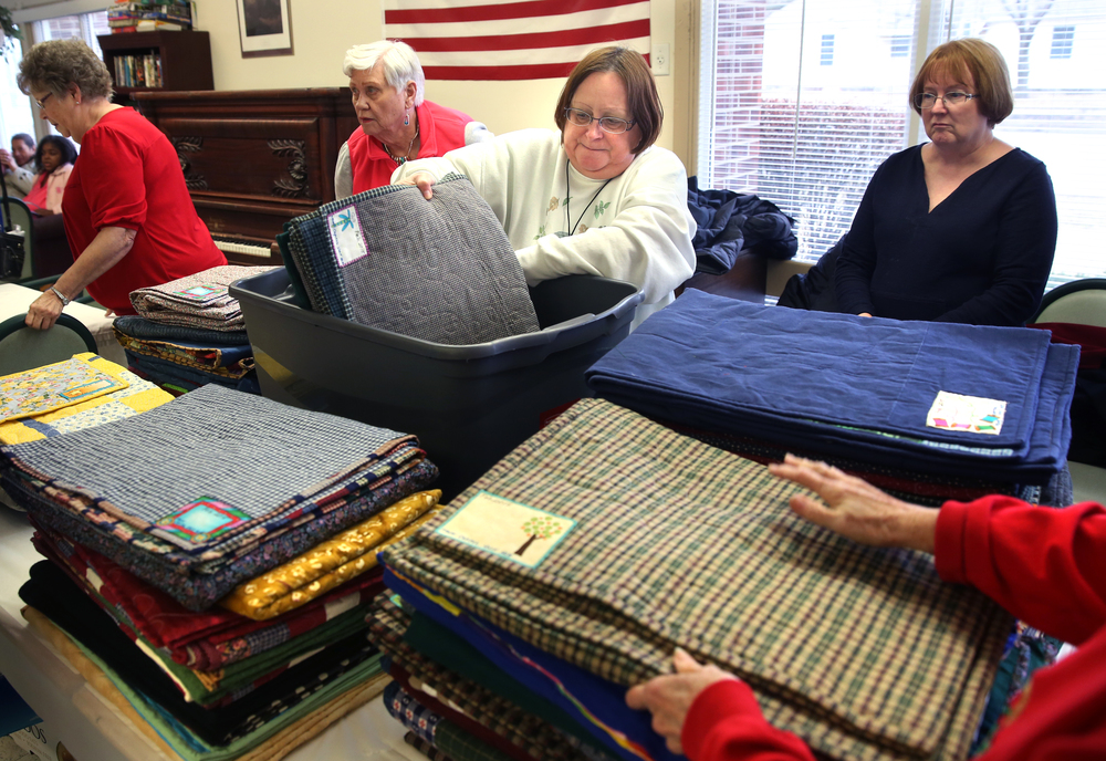 Home and Community Education member Vi Lanum at center removes finished quilts from a tub and stacks them on a table inside the nursing home prior to distribution. David Spencer/The State Journal-Register